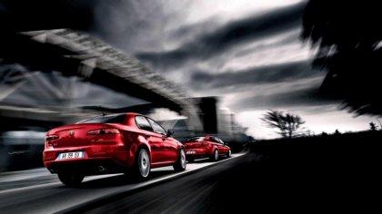 Due vetture rosse dell'alfa romeo in prova sulla strada