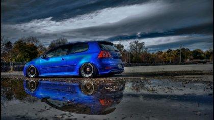 Volkswagen Golf di color Blue con riflesso su asfalto bagnato